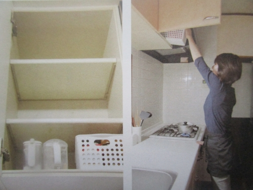 リフォーム前のキッチン 吊戸棚に手を伸ばしている