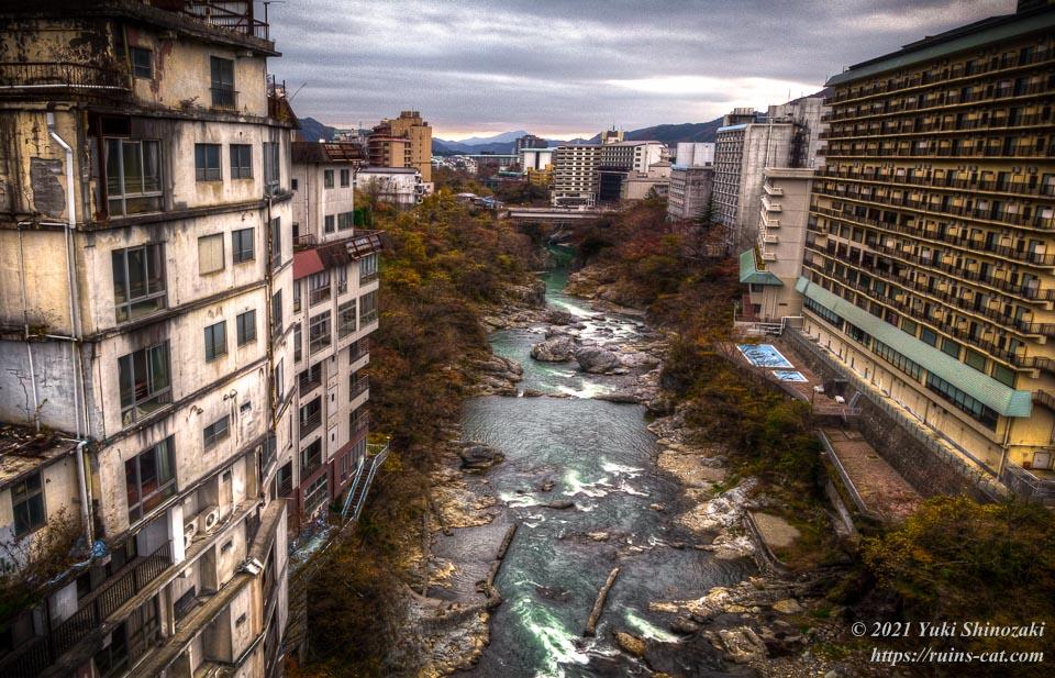 鬼怒川を挟んで廃墟と現役ホテルが向かい合う様子(空撮)
