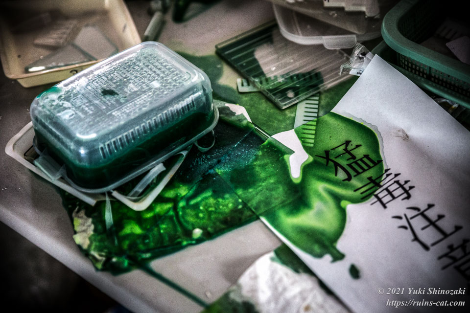飛散した深緑色の謎の液体と「猛毒注意」の注意書き