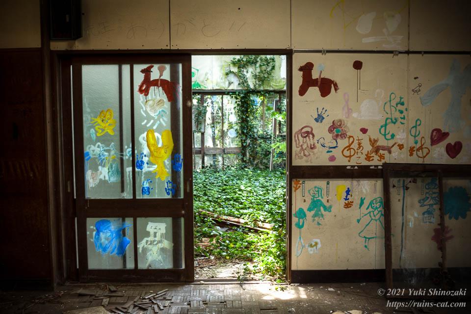 緑の絨毯の教室へと続く扉。上には「先生っありがと!!」の文字。