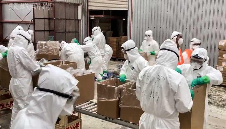 養鶏場で鳥の殺処分を進める防疫職員(茨城新聞より)